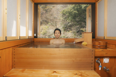 Portrait beautiful young woman soaking in pool at Japanese Onsen