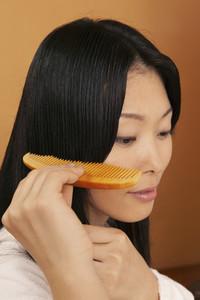Close up beautiful young woman combing hair
