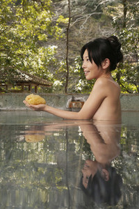 Beautiful young woman with loofah in hot spring water at Onsen