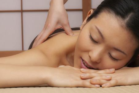 Close up beautiful serene young woman receiving massage at spa