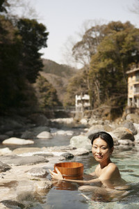 Portrait beautiful young woman with bucket in sunny pool at Onsen