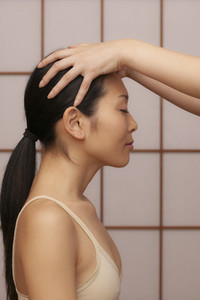 Serene young woman receiving scalp massage at spa
