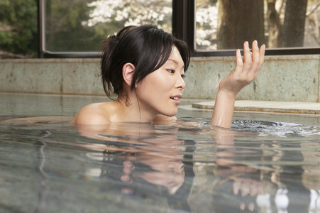 Young woman soaking in water at Onsen spa