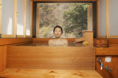 Serene young woman soaking in wooden tub at Japanese Onsen