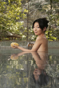 Portrait beautiful nude young woman with loofah in pool at Onsen