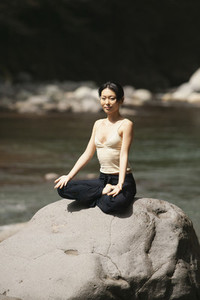 Portrait beautiful young woman meditating in lotus pose on sunny rock
