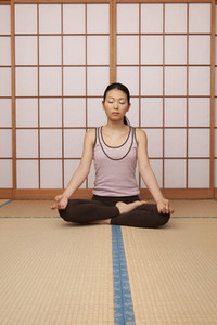Serene young woman meditating in lotus pose on mat