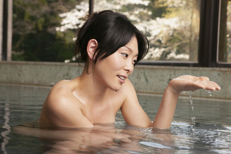 Young woman soaking in pool at Onsen spa