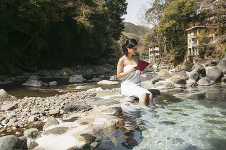 Young woman in towel reading book at sunny pool at Onsen Izu Japan