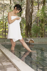 Young woman in towel stepping into pool at Onsen