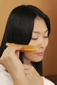 Serene beautiful young woman combing hair