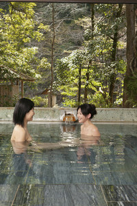 Happy young women talking and soaking in Onsen pool