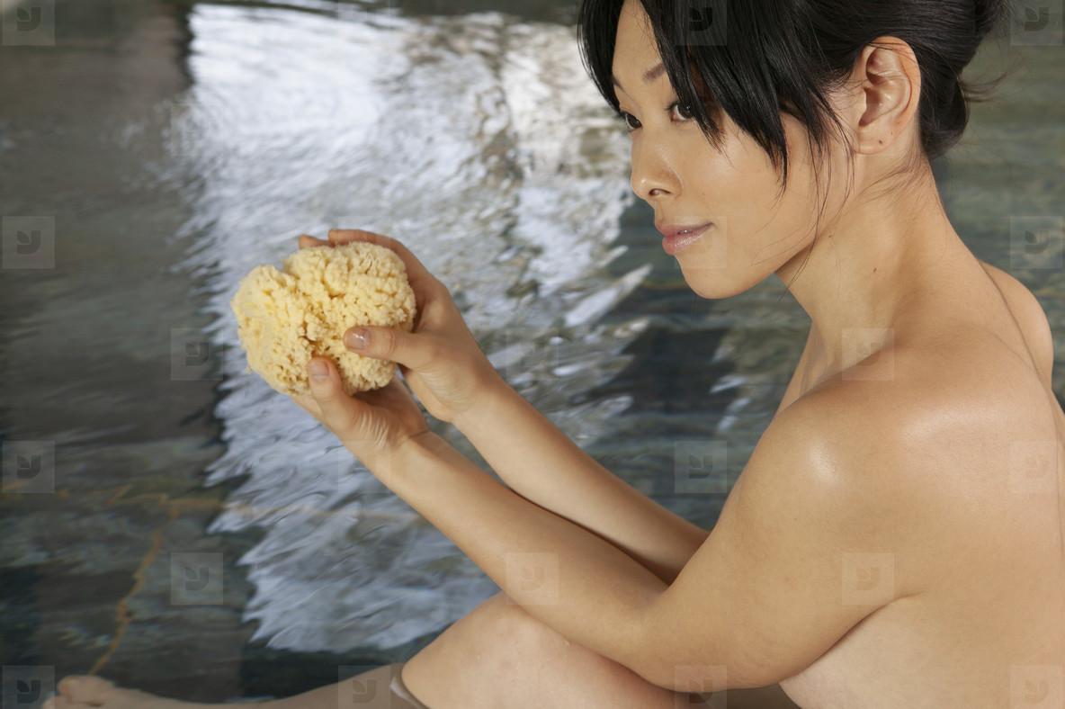Beautiful young woman with loofah soaking in Onsen pool