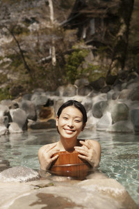 Portrait happy beautiful young woman in sunny pool at Onsen