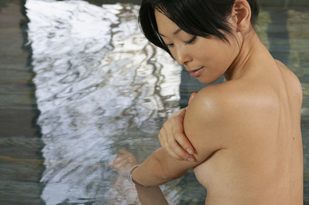 Beautiful nude young woman soaking in pool at spa