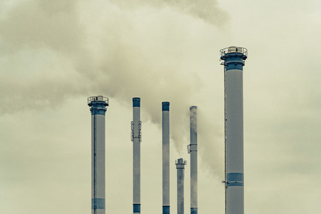 Tall factory smokestacks emitting smoke in sky