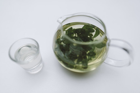 Green loose leaf tea in glass teapot