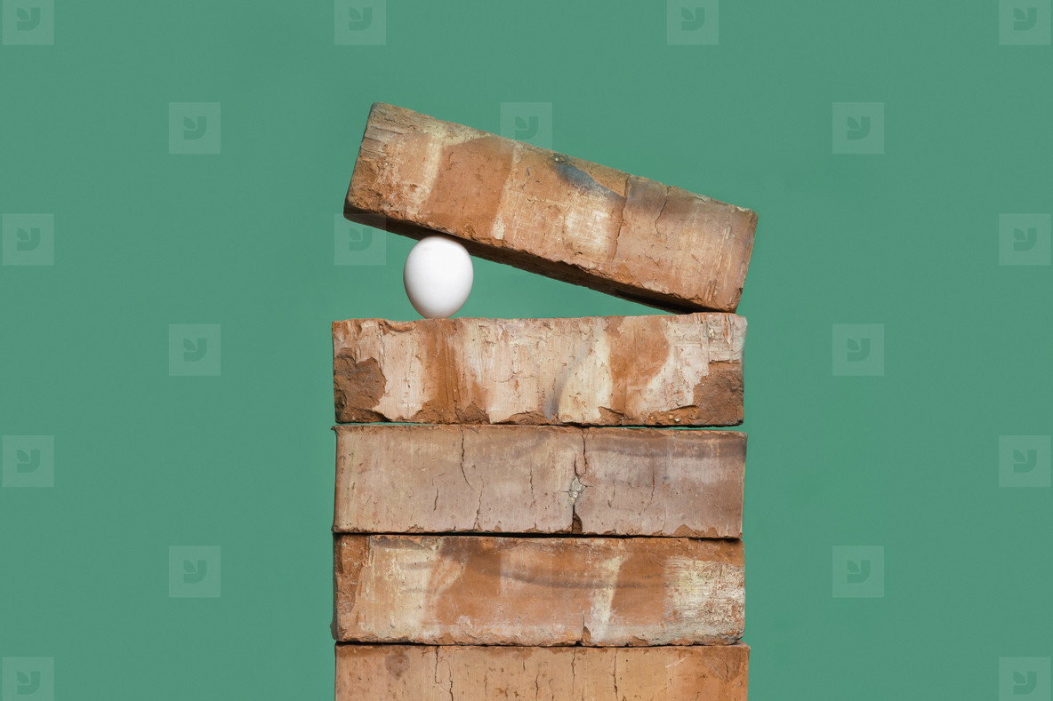 Egg between bricks on green background