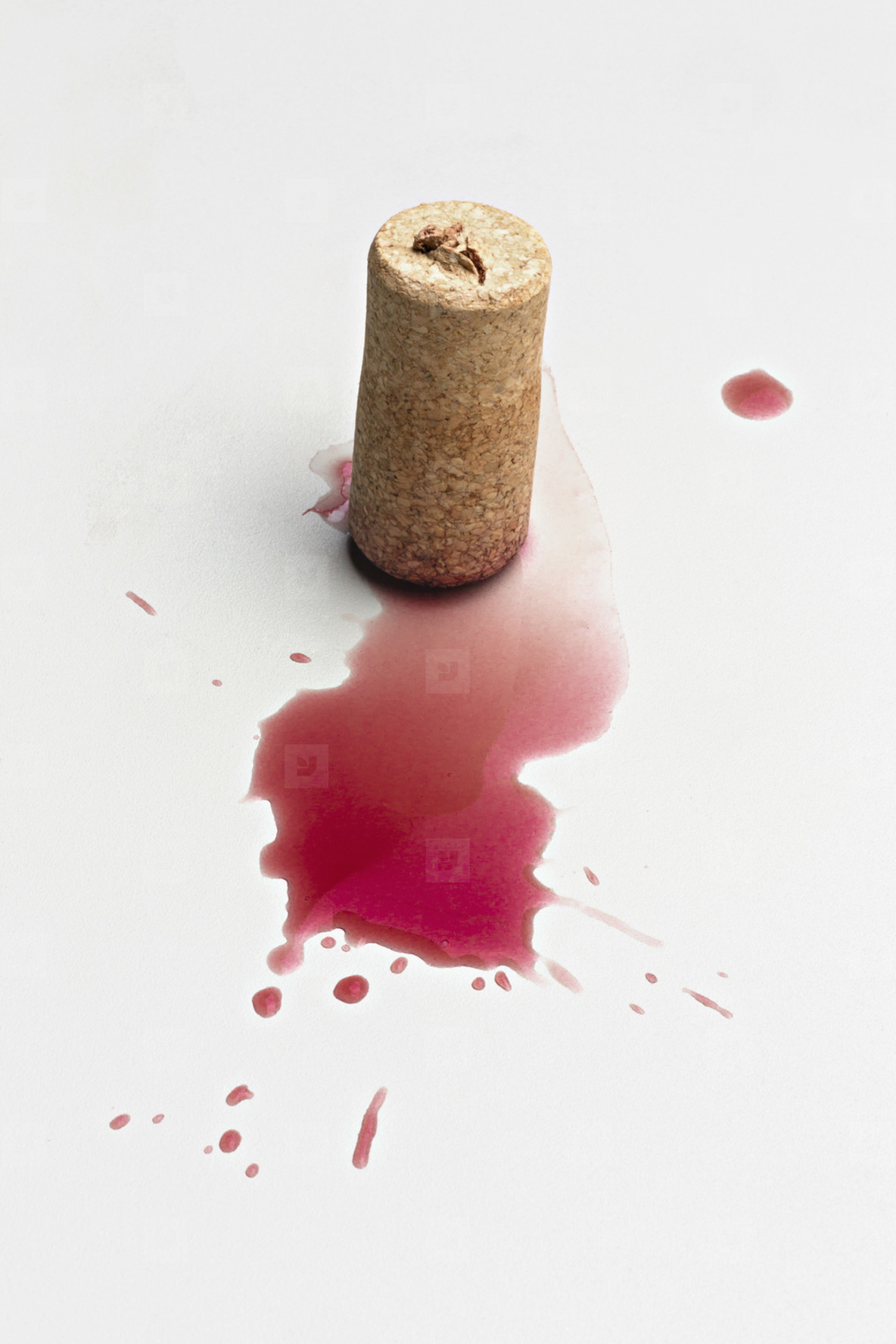Cork and red wine splatter on white background