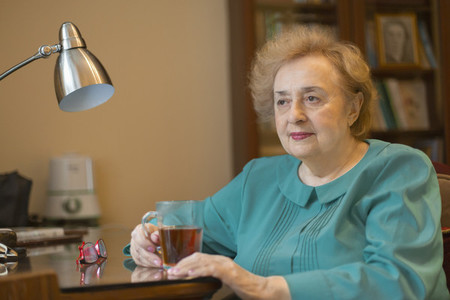 Senior woman drinking tea at desk in home office