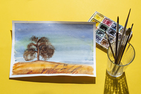 Painting of tree on yellow background with paints and paintbrush