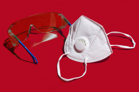 Close up N95 face mask and protective goggles on red background