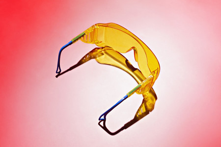 Yellow safety goggles on red background