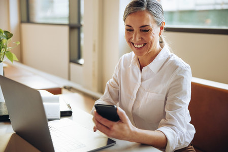 Cheerful businesswoman using cell phone in office
