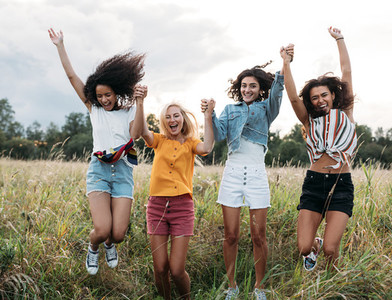 Group of diverse women jumping together outdoors  Friends having fun during vacation