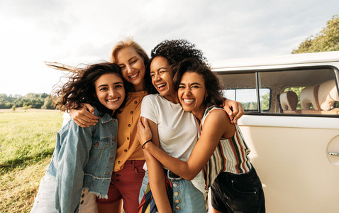 Four happy female friends laughing together standing in front of a van  Women enjoying summer road trip