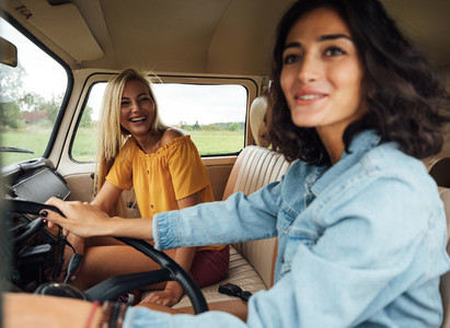 Smiling blond woman on a passenger seat looking at her friend while traveling by a van