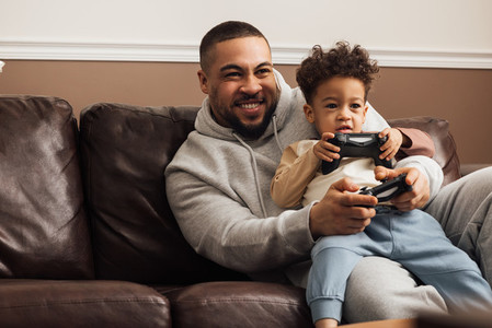 Excited father and son playing video game on a console at home