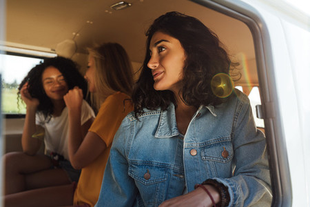 Three women sitting together in van during road trip