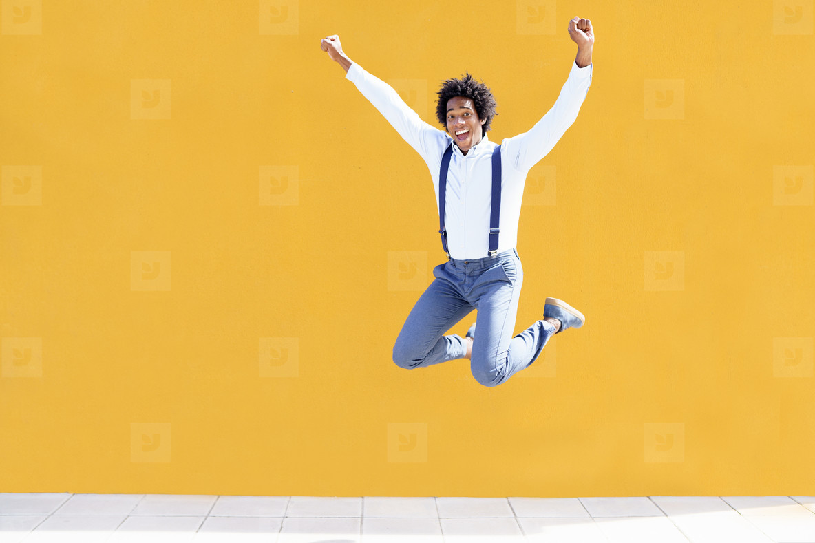 Black man with afro hair jumping on a yellow urban background