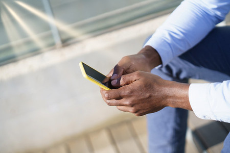 Hands of unrecognizable black man using a smartphone