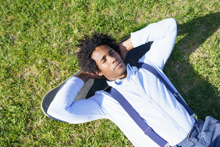 Black businessman resting lying on the grass with his skateboard