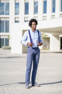 Black businessman wearing shirt and suspenders standing near an office building