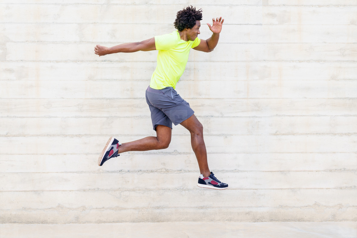 Black man training running jumps to strengthen his legs