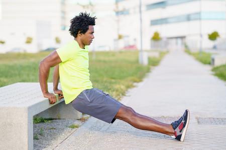 Black man doing triceps dip exercise on city street bench