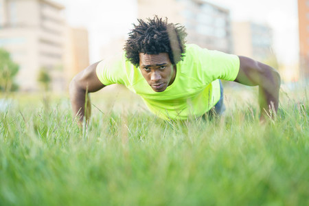 Black man doing push ups exercising his chest on the grass of an urban park