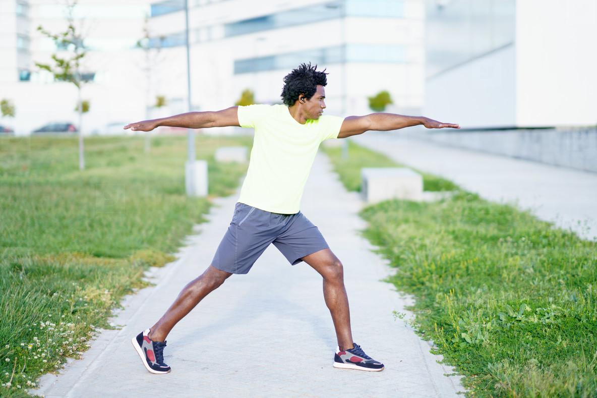 Black man doing Warrior 2 or Virabhadrasana II pose outdoors