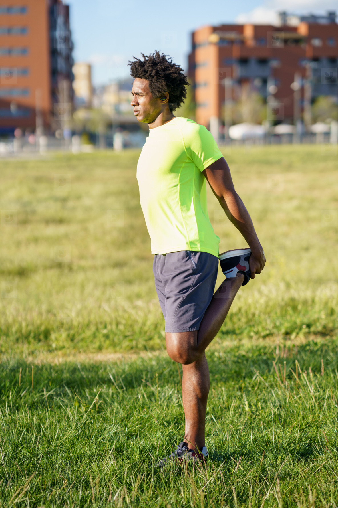 Black man stretching his quadriceps after running outdoors