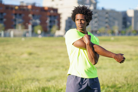 Black man with afro hair doing stretching after running outdoors