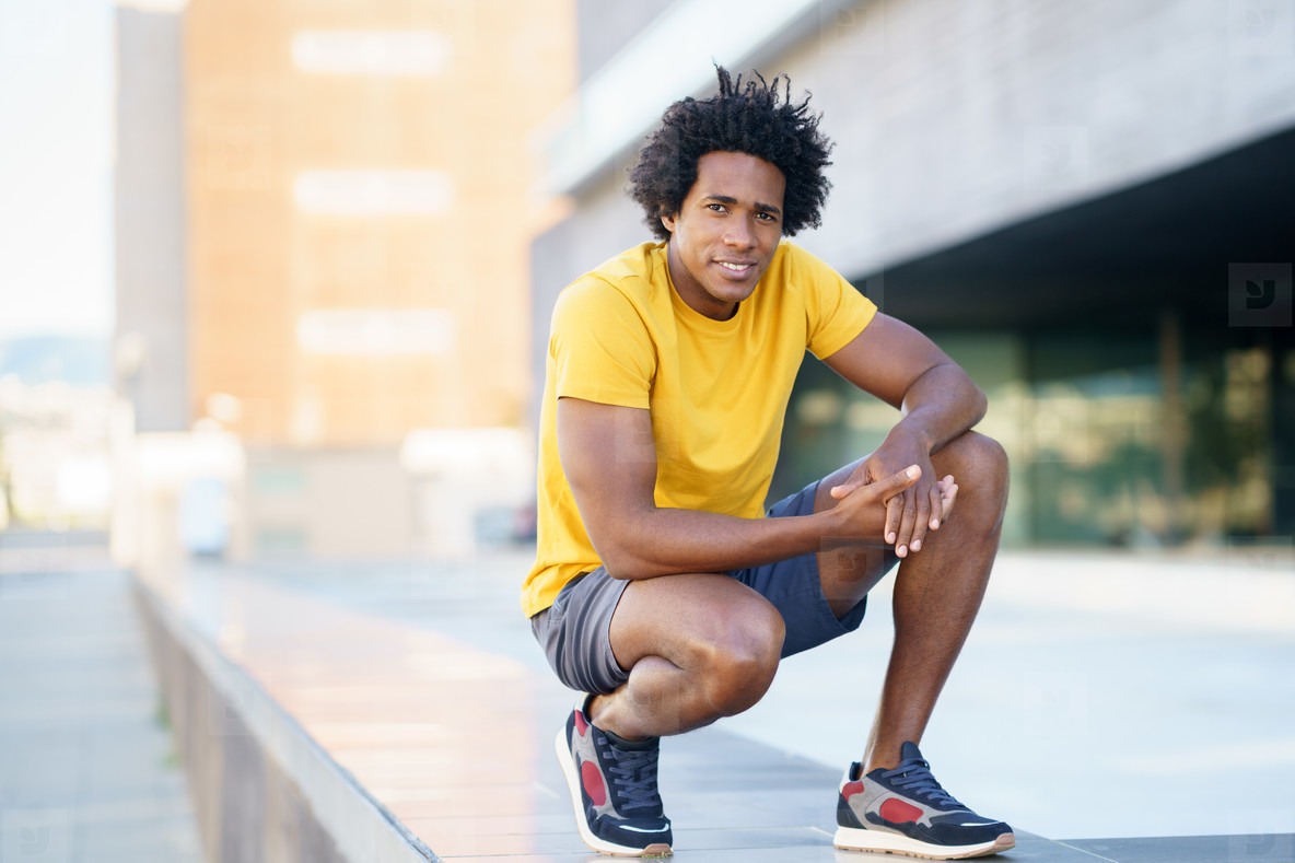 Black man with afro hair taking a break after workout