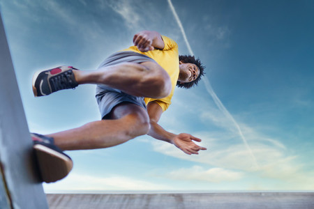 View from below of black man jumping on his run