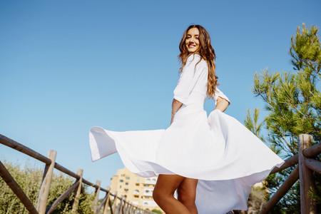 Young woman wearing a beautiful white dress enjoying a natural environment