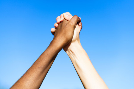 Multiethnic womens hands together against blue sky