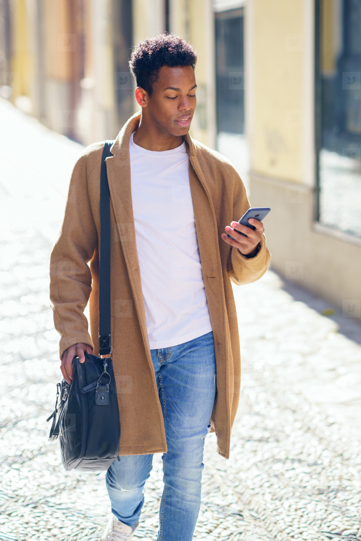 Young black man walking down the street carrying a briefcase and a smartphone