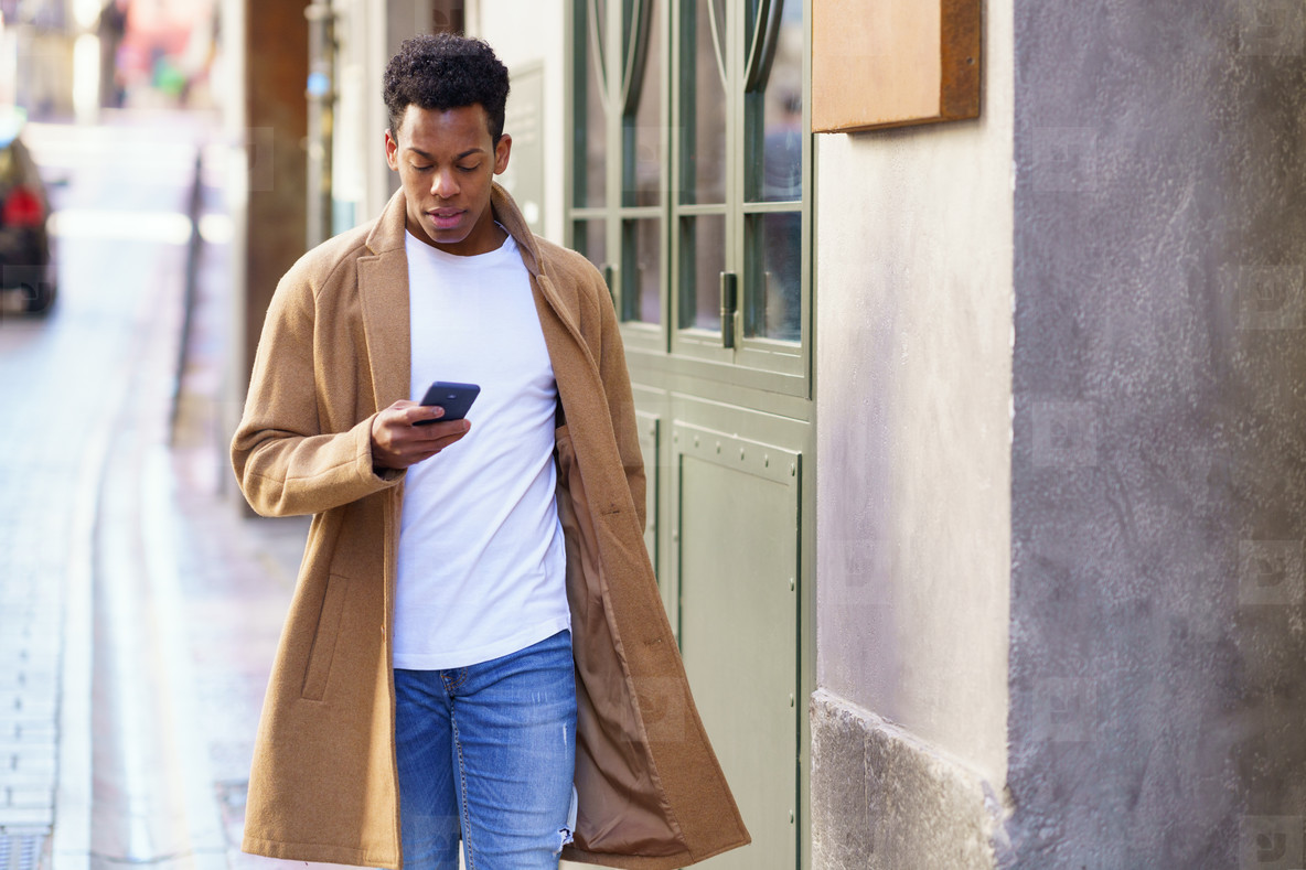 Young black man consulting his phone while walking down the street
