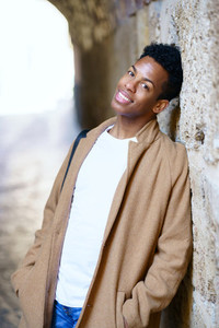 Young black man looking at camera with a happy hopeful look on his face outdoors